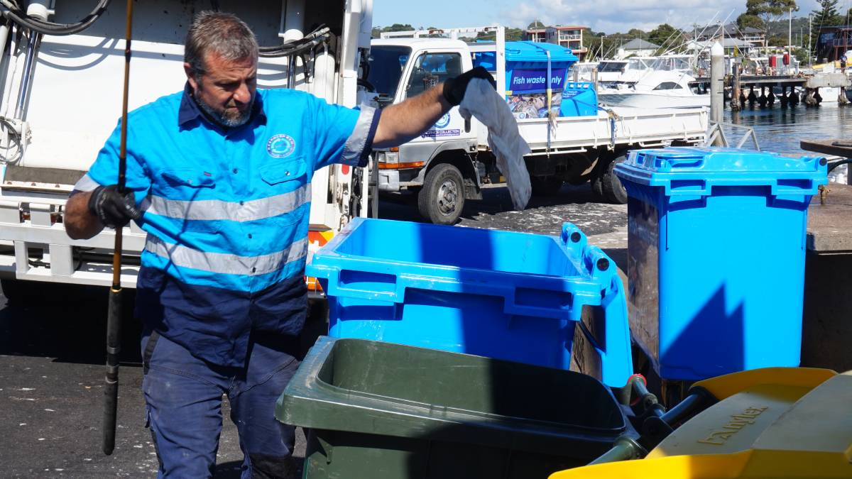 Tim Crane pulls plastic out of the fish waste bins at Bermagui's harbour.
